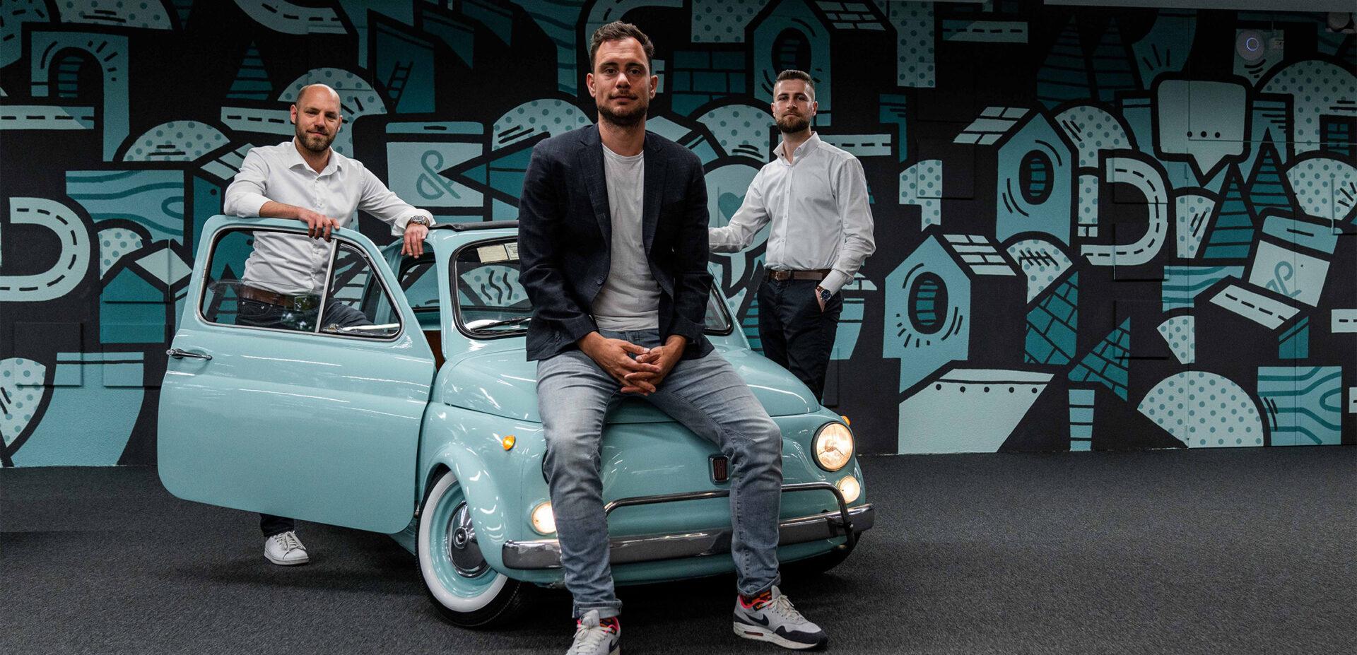 Die ads&figures Gründer vor dem Fiat 500 im Büro